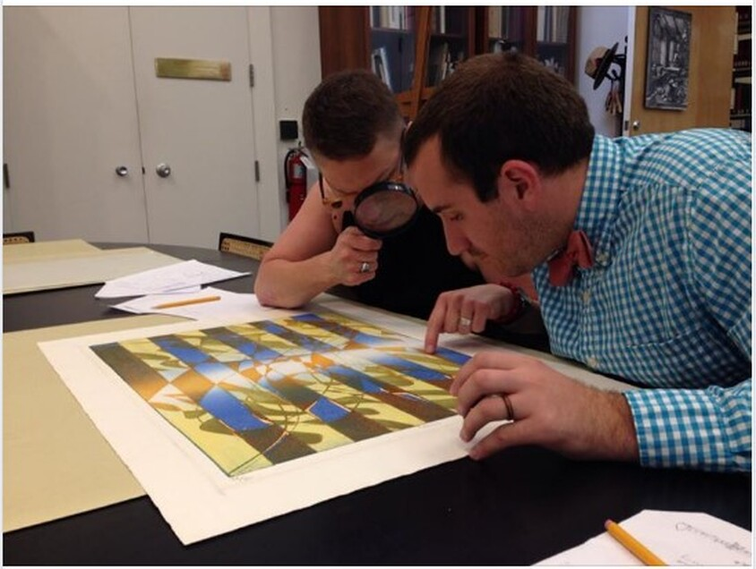 Picture of Ben Levy and Tru Ludwig looking at Hayter's print, Pillars, 1974.